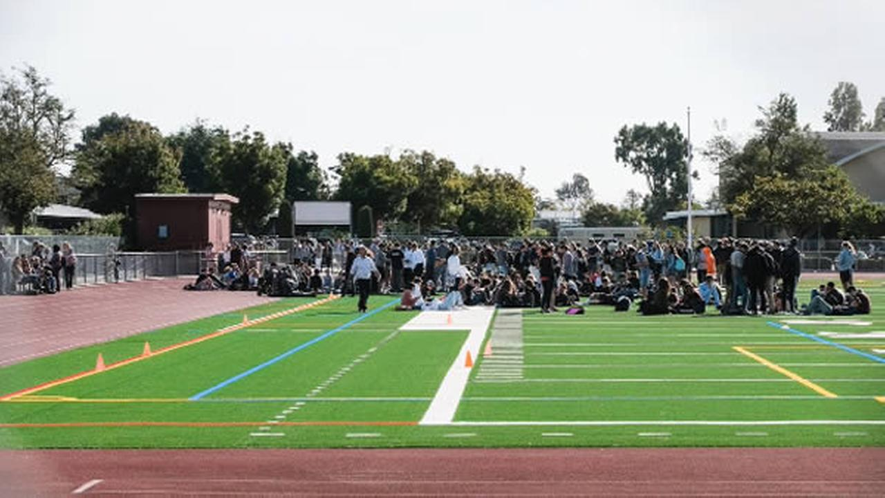 Students are seen standing in a football field after a bomb scare at Redwood High School in Larkspur, Calif. on Tuesday, September 19, 2017.
