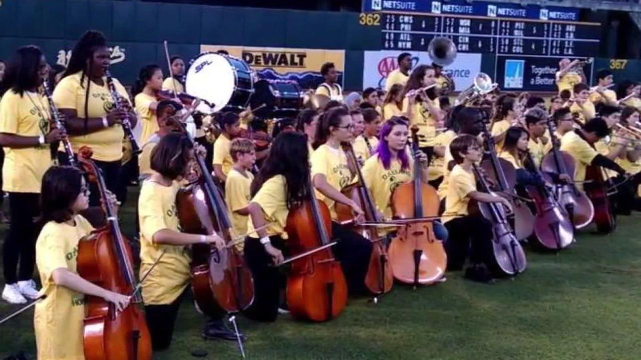 Members of the OUSD honor band kneel in protest while playing the National Anthem at an Oakland Athletics game on Monday, Sept. 25, 2017.