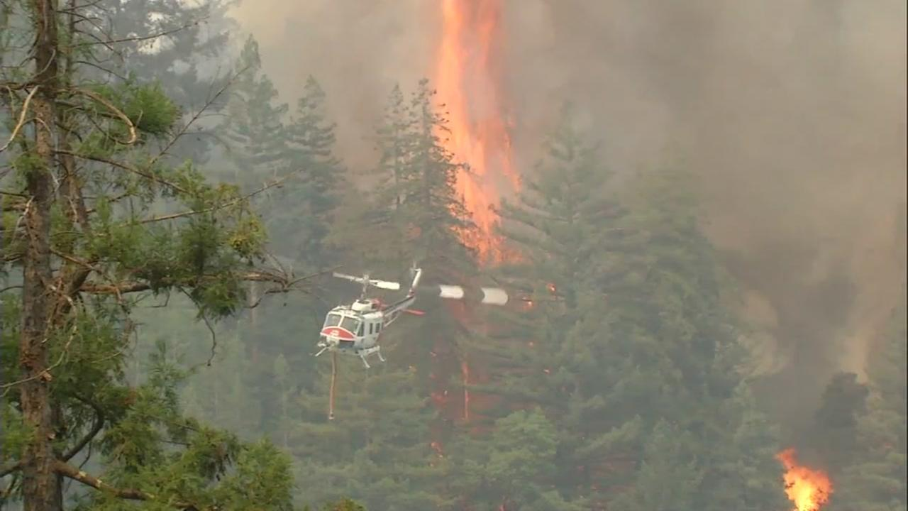 A helicopter is seen flying over the Bear Fire on Wednesday, October 18, 2017.