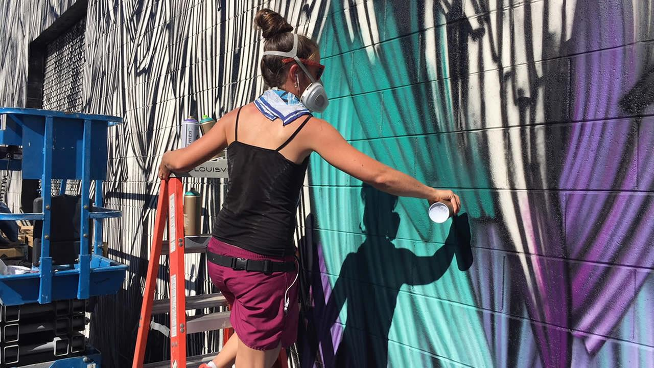 Adele Renault from Amsterdam works on a mural in San Jose, Calif. on Monday, Oct. 23, 2017.