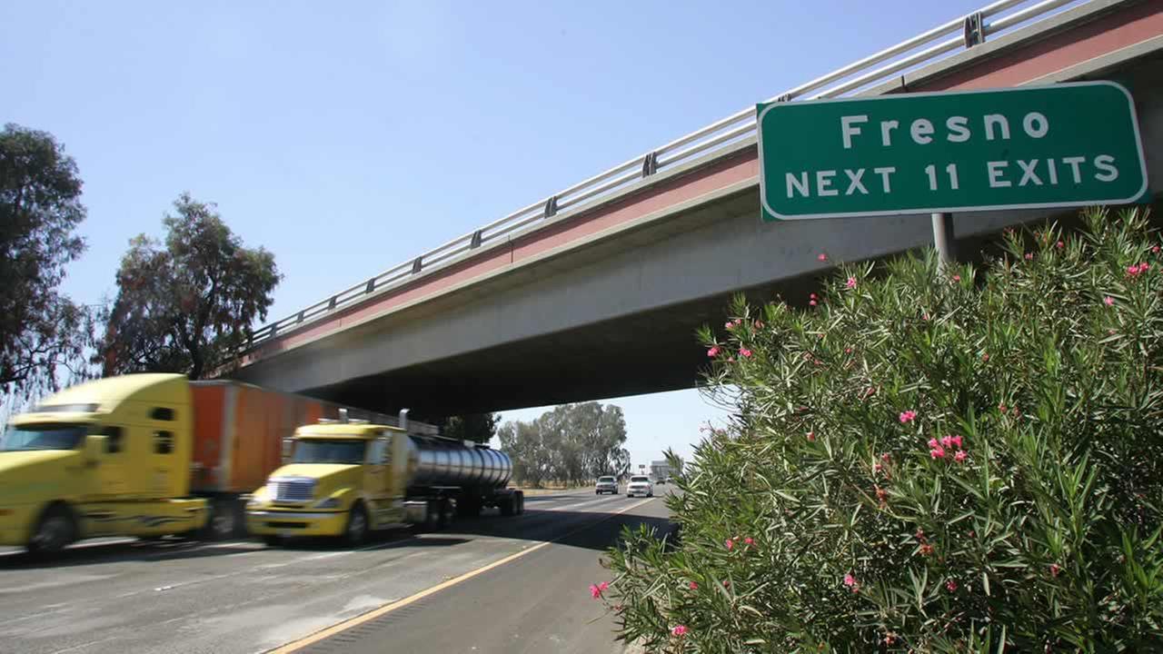 Trucks fly by a Fresno sign on Calif. State Route 99 Tuesday, Aug. 23, 2011, in Fresno, Calif. (AP Photo/Gary Kazanjian)
