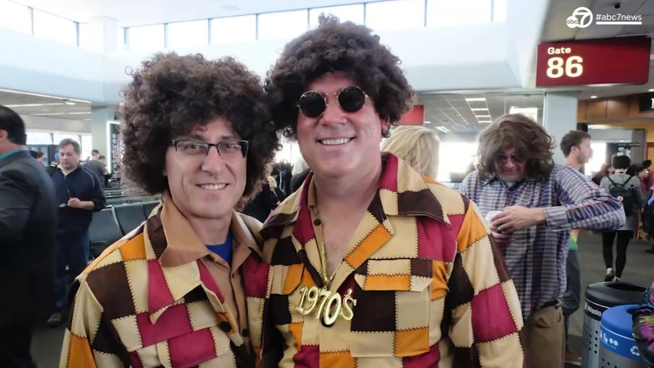 Two United Airlines passengers in costume pose before boarding their flight on Tuesday, Nov. 7, 2017 in San Francisco.