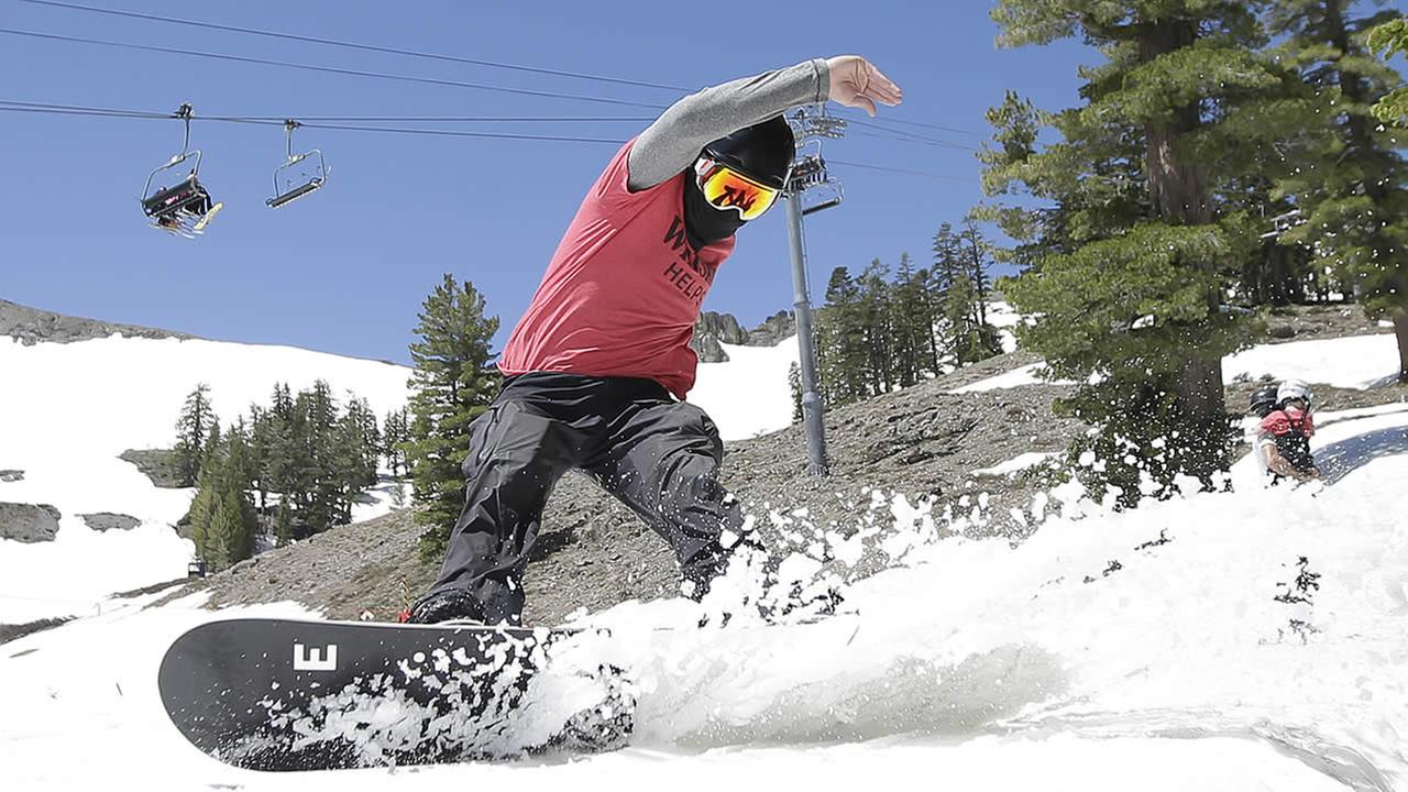 In this July 1, 2017 file photo, a snow boarder cuts throughout the snow at the Squaw Valley Ski Resort in Squaw Valley, Calif.