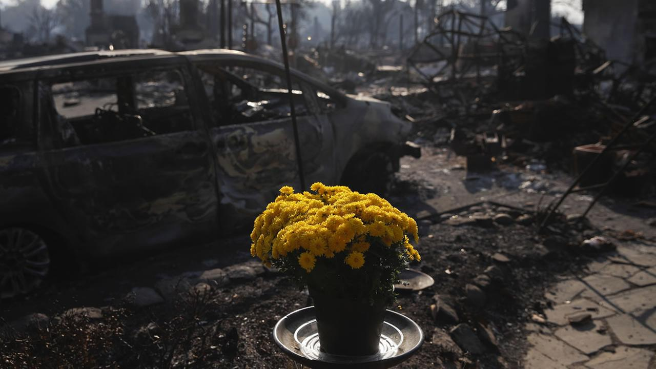 Fresh flowers are placed, Sunday, Oct. 15, 2017, in the Coffey Park neighborhood in Santa Rosa, Calif., that was devastated by a wildfire.