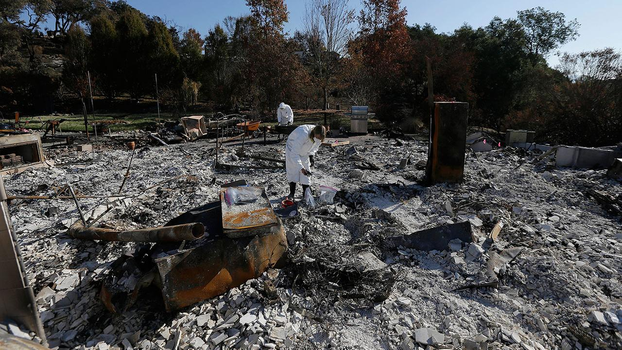 In this Tuesday, Oct. 31, 2017 photo, Shelly Rust, foreground, and her husband David search through the remains of their home destroyed by wildfires in Santa Rosa, Calif.