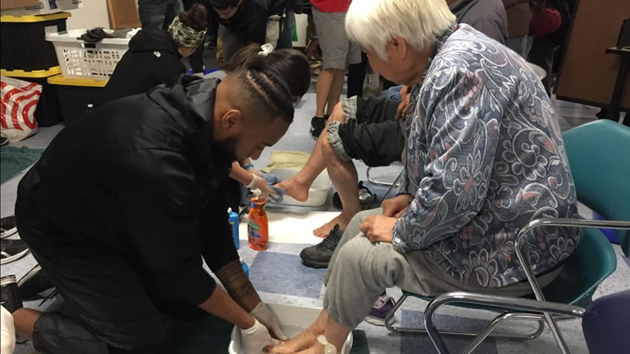 This image shows a volunteer washing the feet of a woman in San Jose, Calif. on Thursday, Nov. 23, 2017