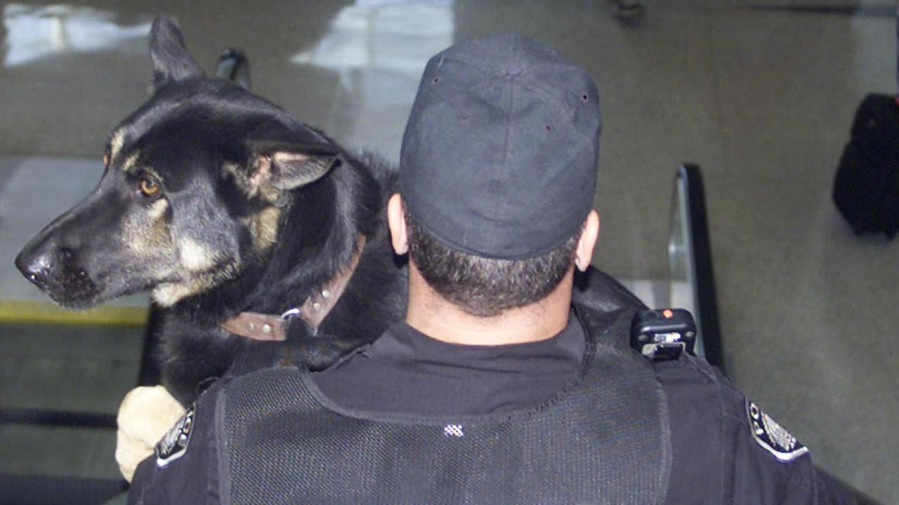 A police officer carries a dog trained to find explosives down an escalator at the Cincinnati/Northern Kentucky International Airport, Sept. 11, 2001, in Hebron, Ky. (AP Photo/Al Behrman)