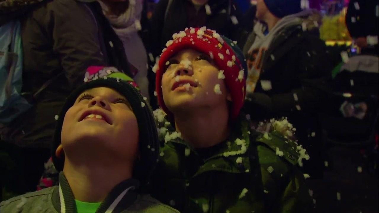 Two kids look up at the snow falling at Great Americas Winterfest in Santa Clara, Calif. on Thursday, Dec. 21, 2017.
