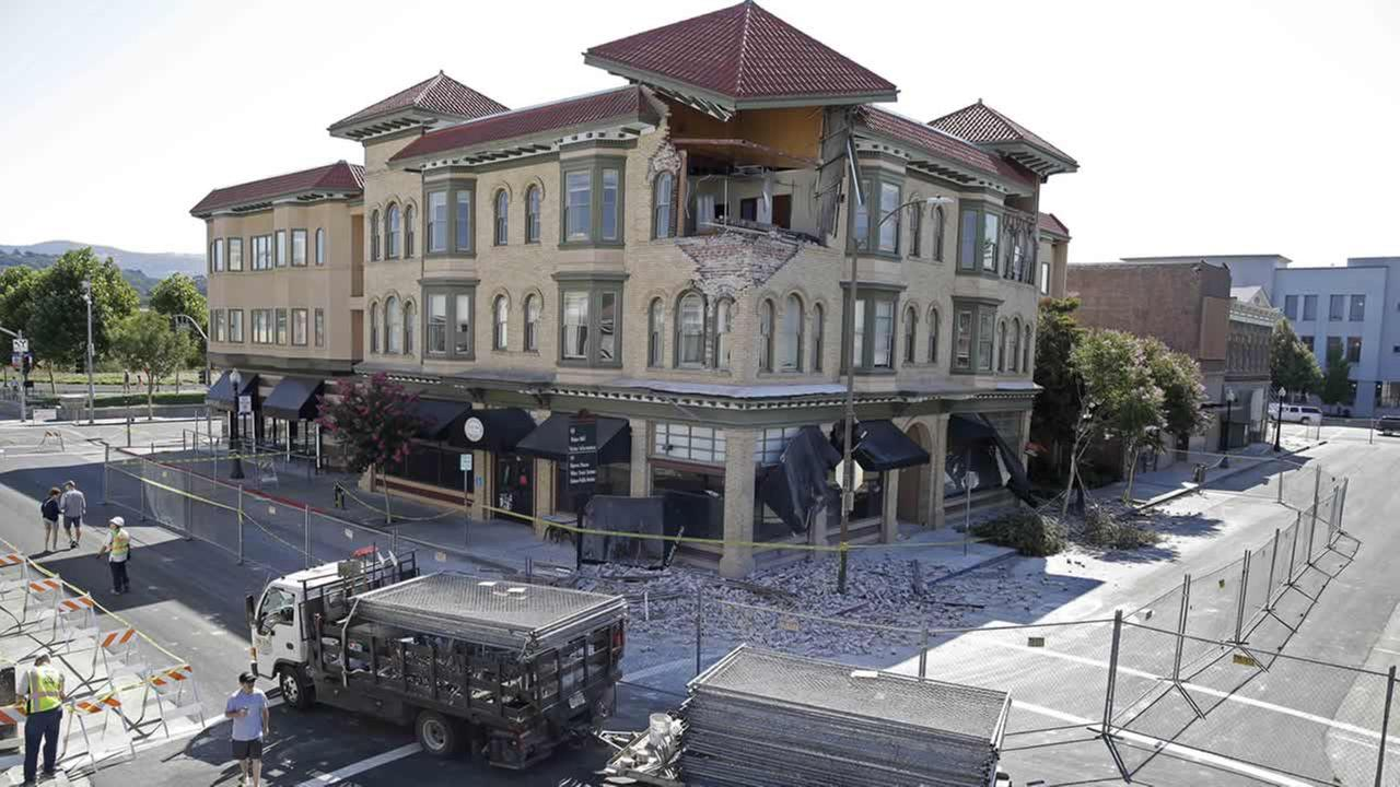 A truckload of fencing is brought to Second Street outside the earthquake damaged building that housed the Carpe Diem wine bar Tuesday, Aug. 26, 2014, in Napa, Calif. (AP Photo/Eric Risberg)