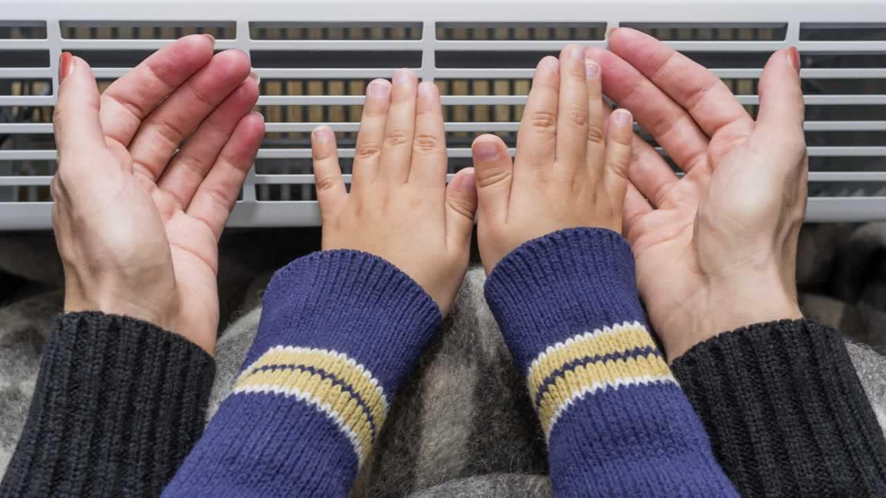 A family holds their hands in front of a heater in this undated file photo.