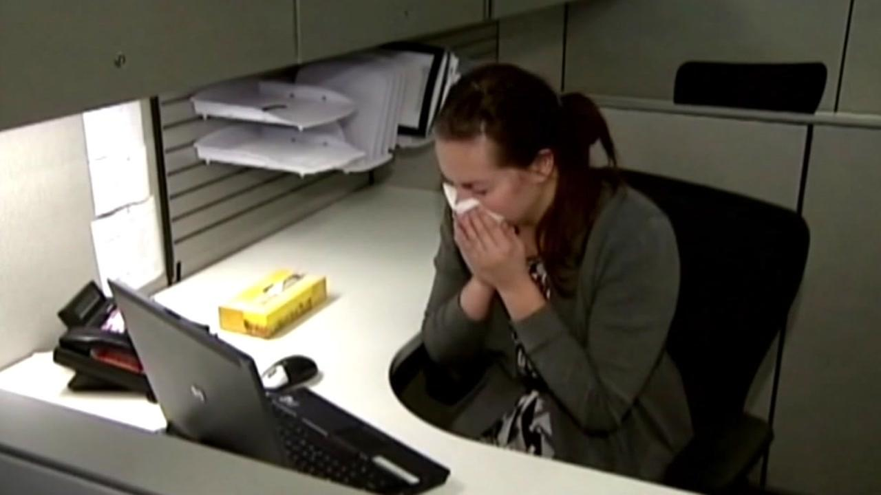 A woman sneezes into a tissue at her desk in this undated file photo.