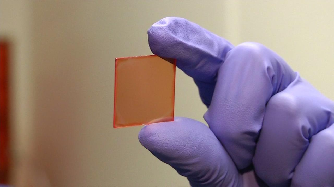 Chemistry professor Peidong Yang holds up a small square of orange-tinted glass on Monday, Jan. 29, 2018 in Berkeley, Calif.