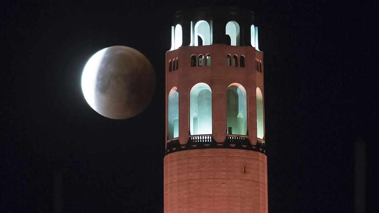 A partially-eclipsed super blue blood moon sets behind Coit Tower, on Wednesday, Jan. 31, 2018, in San Francisco.(AP Photo/Noah Berger)