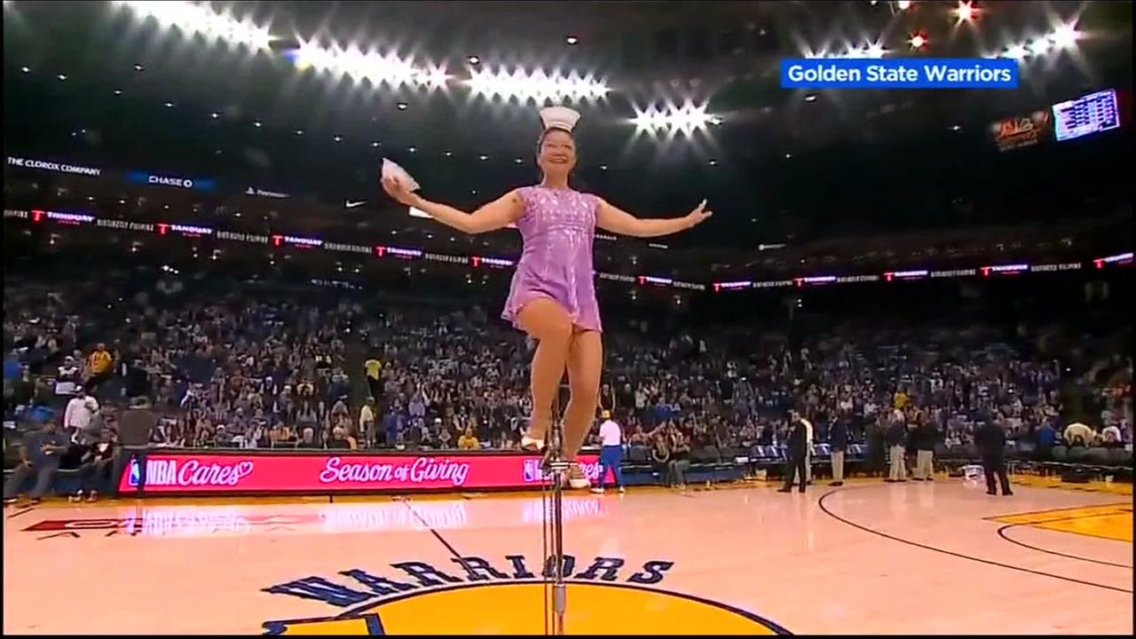 Red Panda rides on her unicycle during a Warriors game.