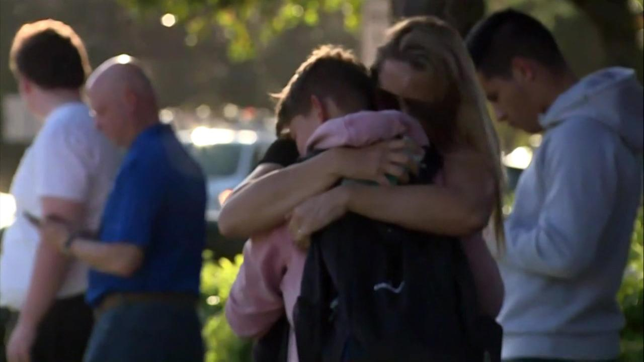 A mother hugs her child outside the school in Parkland, Fla. where 17 people were killed in a devastating school shooting on Wednesday, Feb. 14, 2018.