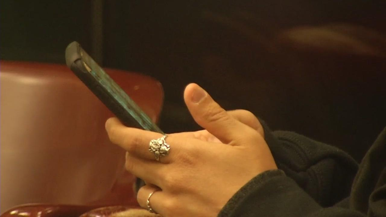 A person holding a phone appears in this undated image.