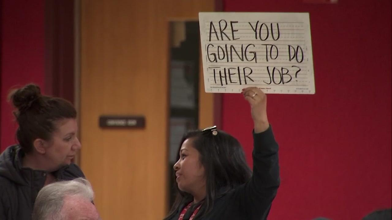 A woman holds up a protest sign at a meeting regarding teachers in San Jose, Calif. on Thursday, March 8, 2018.