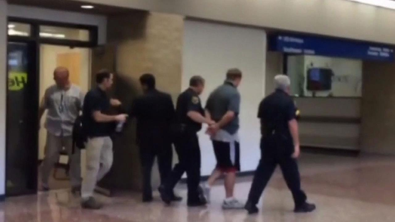 Doug Adams of Woodside being arrested at an airport