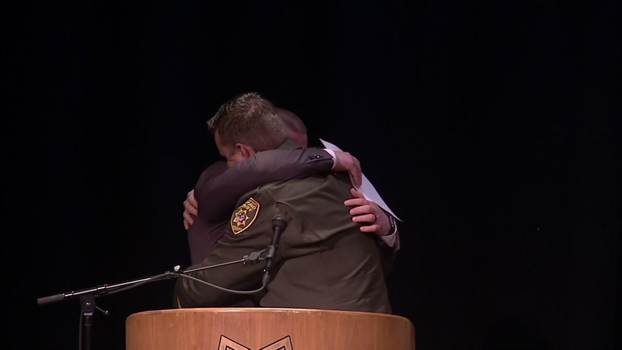 Officials hug at a memorial for Marin County Sheriffs Deputy Ryan Zirkle on Friday, March 23, 2018.
