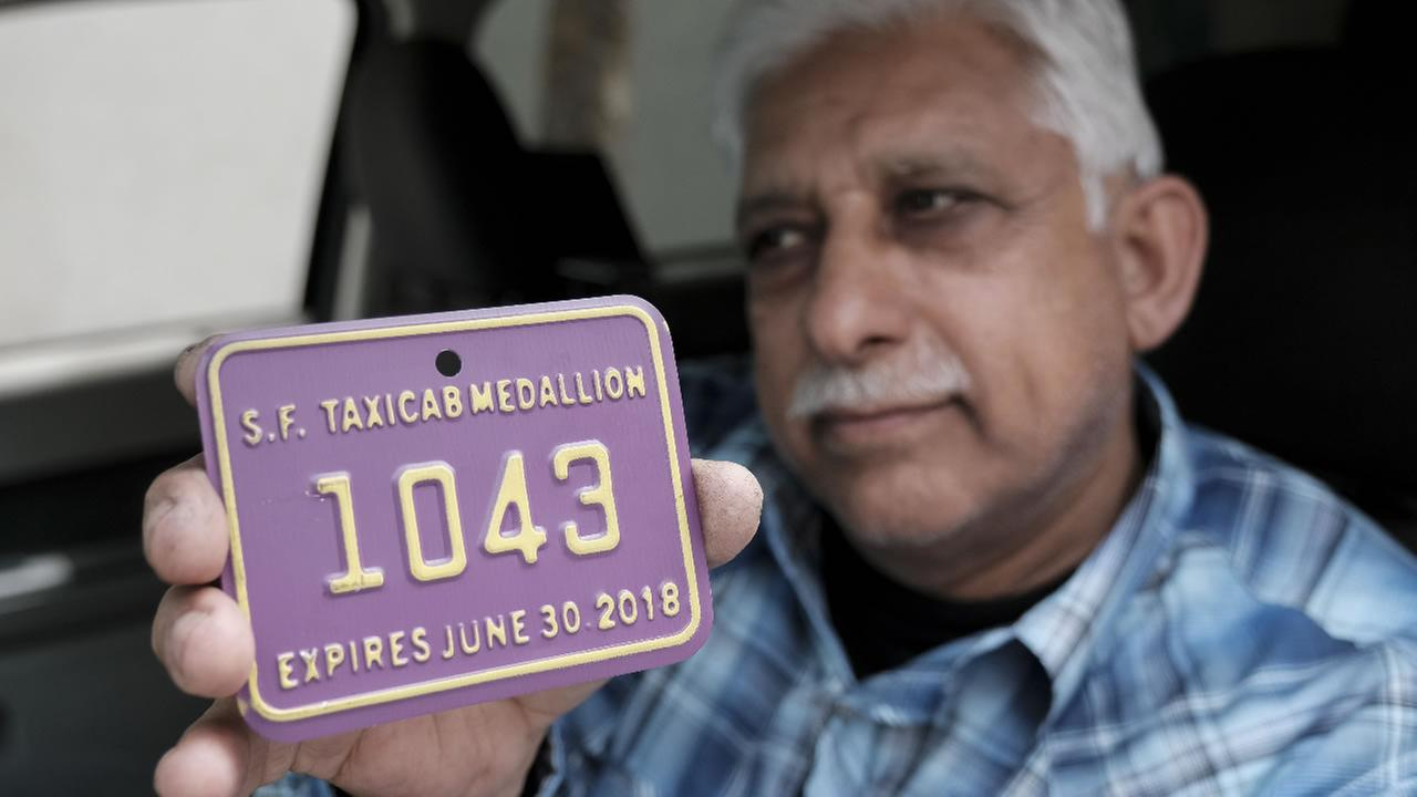 A San Francisco taxi driver holds up his taxi medallion on Friday, March 30, 2018.