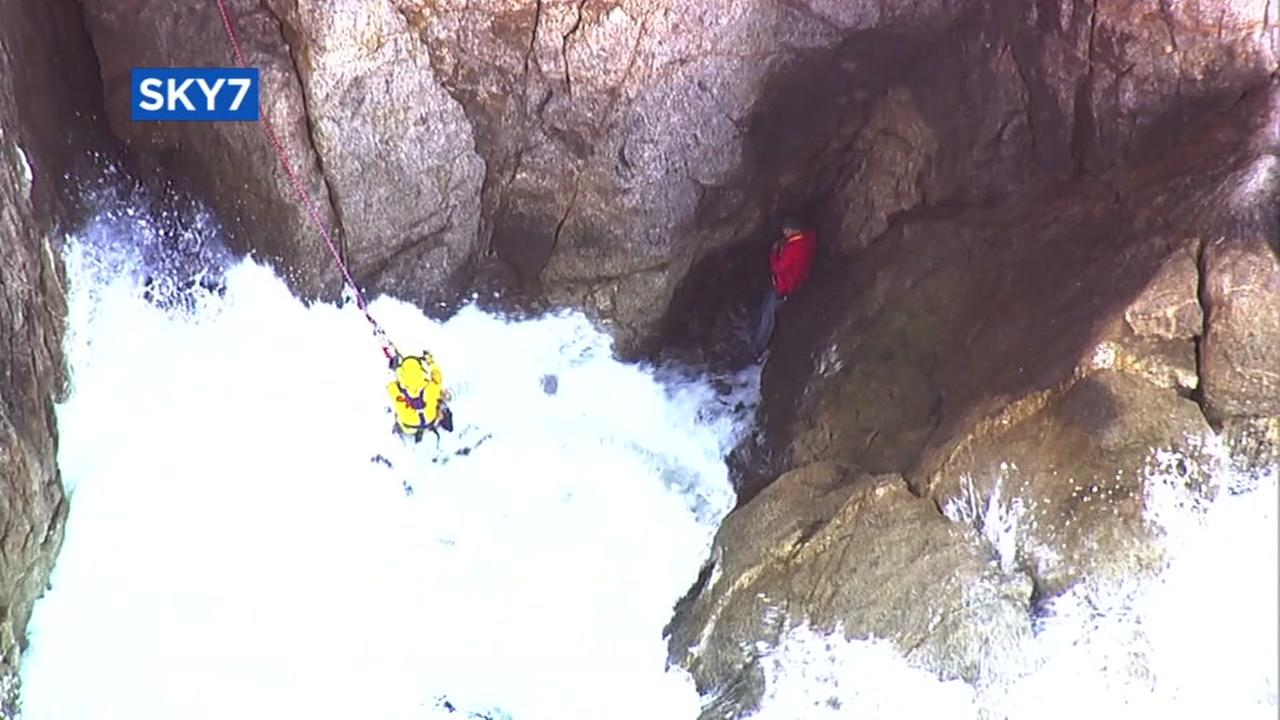 A rescuer reaches a man who plunged off a cliff in Montara, Calif. on Friday, April 13, 2018.