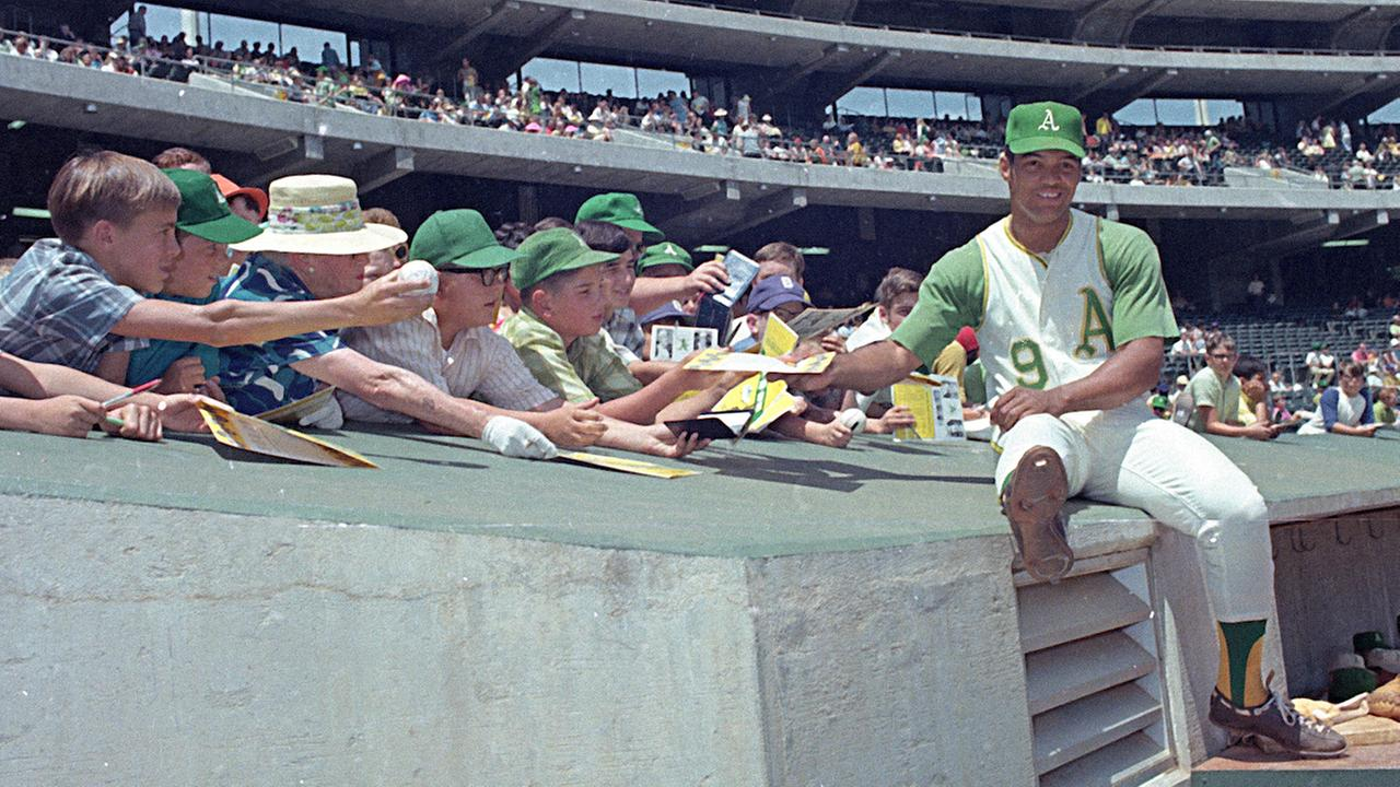 Oakland Athletics player Reggie Jackson signs autographs for fans in front of the dugout at the Oakland Coliseum.