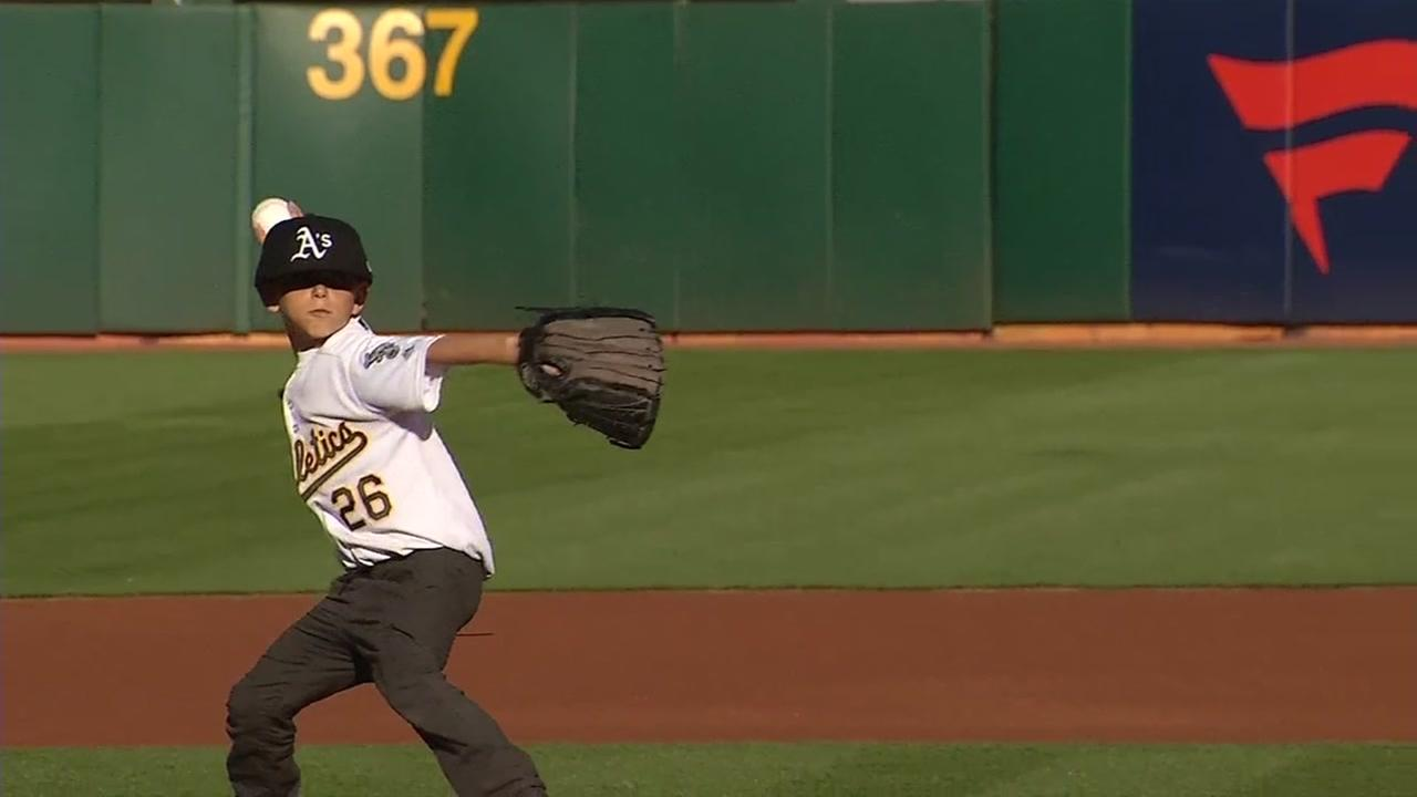 Loren Smith throws the first pitch during an Oakland Athletics game in Oakland, Calif. on Saturday, April 21, 2018.