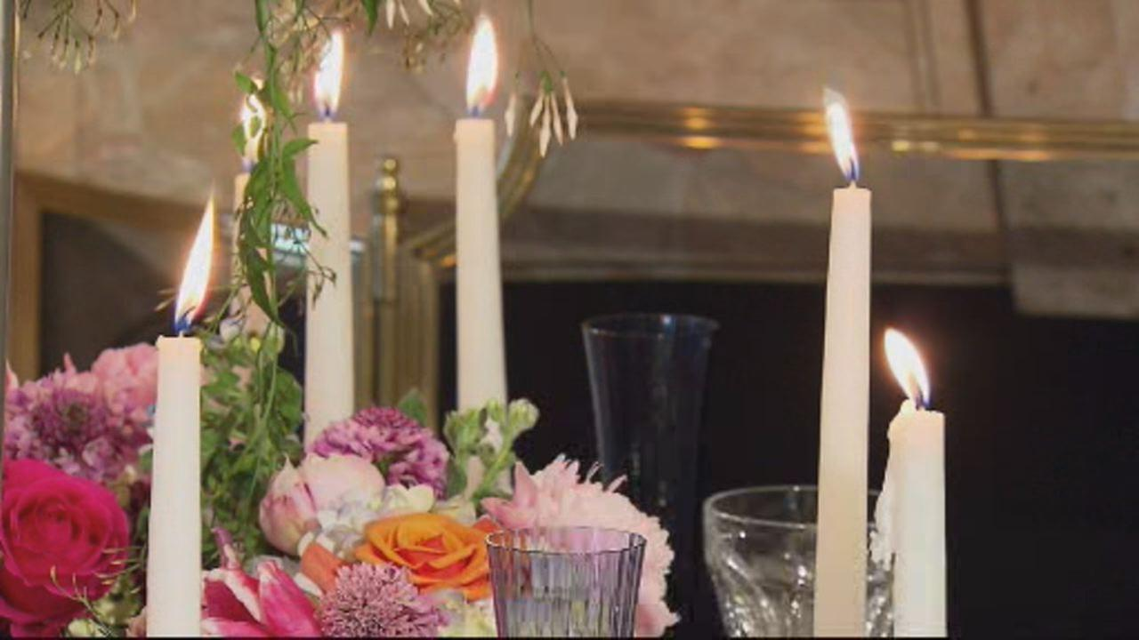 This undated image shows wedding reception table decorated with candles and flowers.