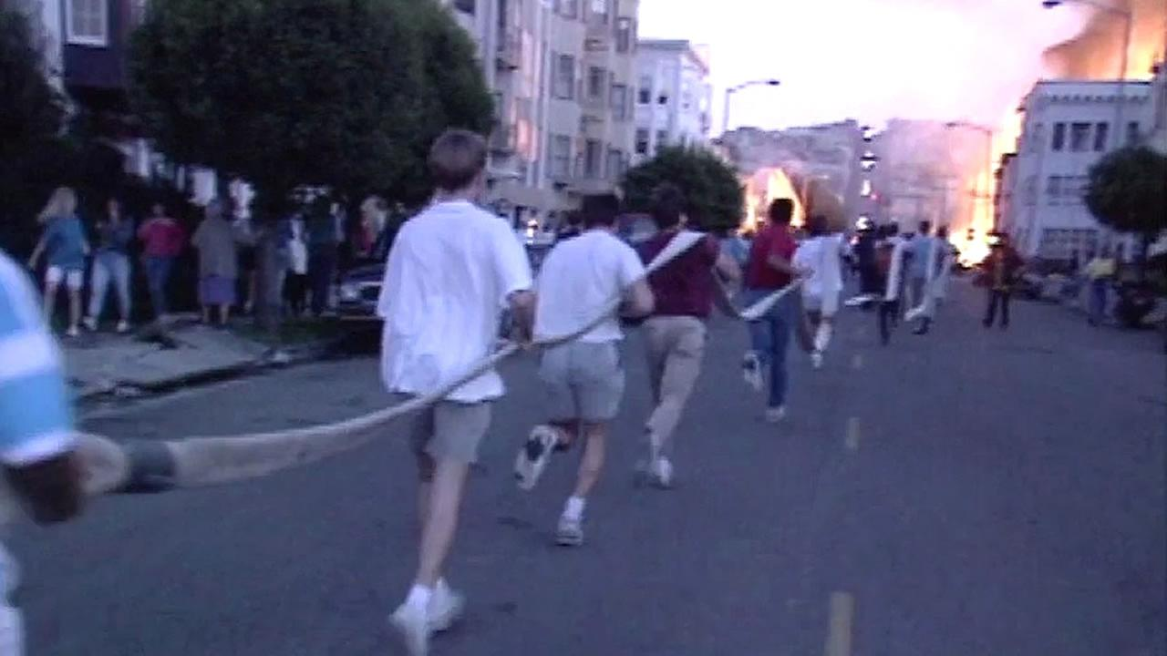 1989 Loma Prieta earthquake, men carry fire hose in Marina
