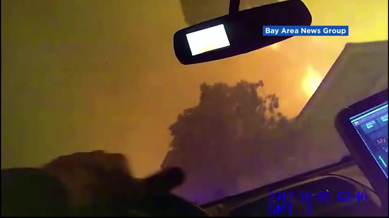 Undated photo shows Santa Rosa police evacuating houses during wildfires in Santa Rosa, California.