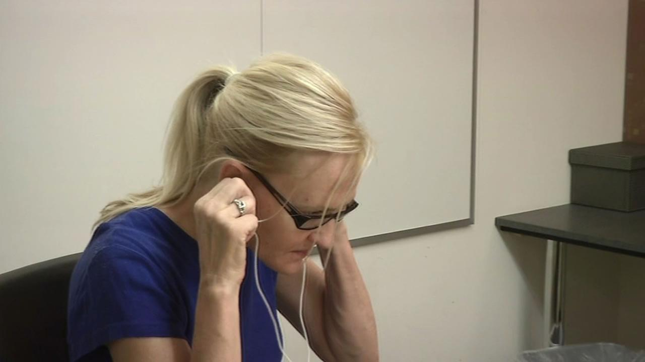 woman listening to a hearing test through earbuds