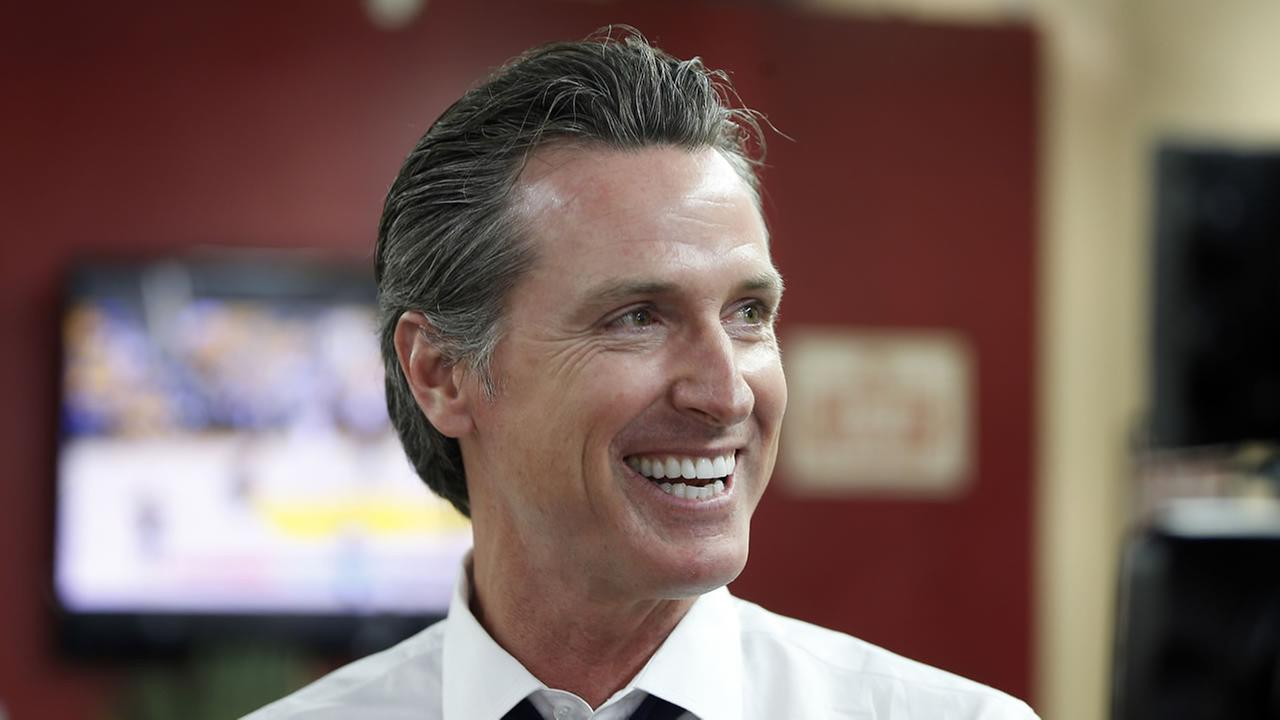 In this May 31, 2018 file photo Democratic Lt. Gov. Gavin Newsom smiles at a campaign stop at Stakelys Barber Salon in Los Angeles.