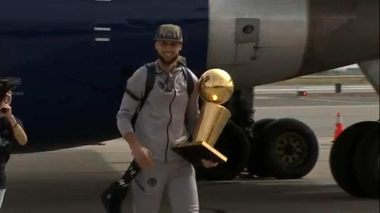 Steph Curry holds his NBA trophy as he deplanes in Oakland on June 9, 2018, the day after the Golden State Warriors beat the Cleveland Cavaliers to win the NBA Finals.