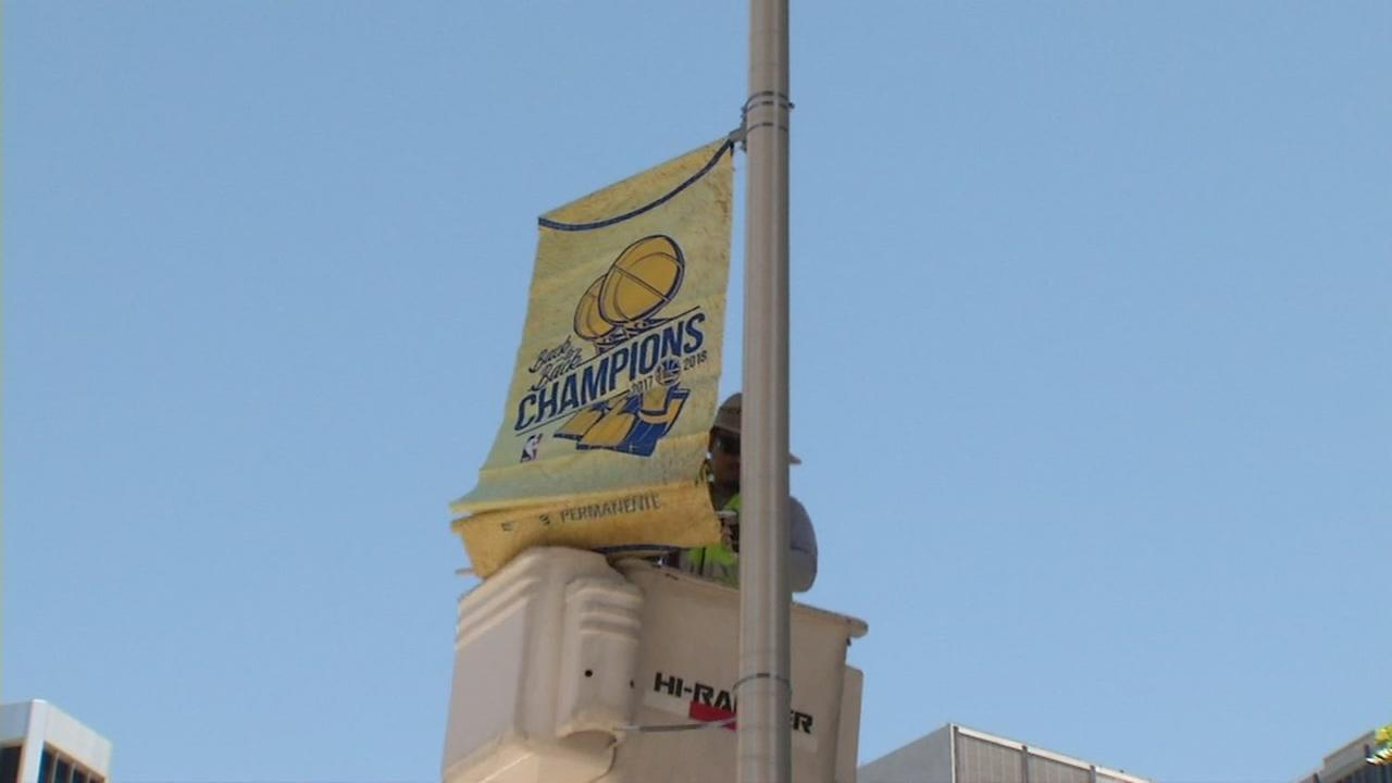 Crews unfurl banners for the Golden State Warriors 2018 victory parade on Sunday, June 10, 201 in Oakland, Calif.