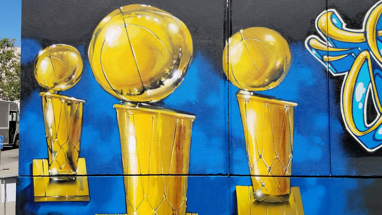 An Oakland artist puts the finishing touches on a new mural depicting the Warriors three championship trophies at the Oakland Convention Center.