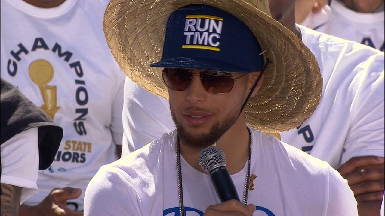 Stephen Curry wears a Run TMC hat while speaking before the Warriors victory parade in Oakland, Calif. on Tuesday, June 12, 2018.