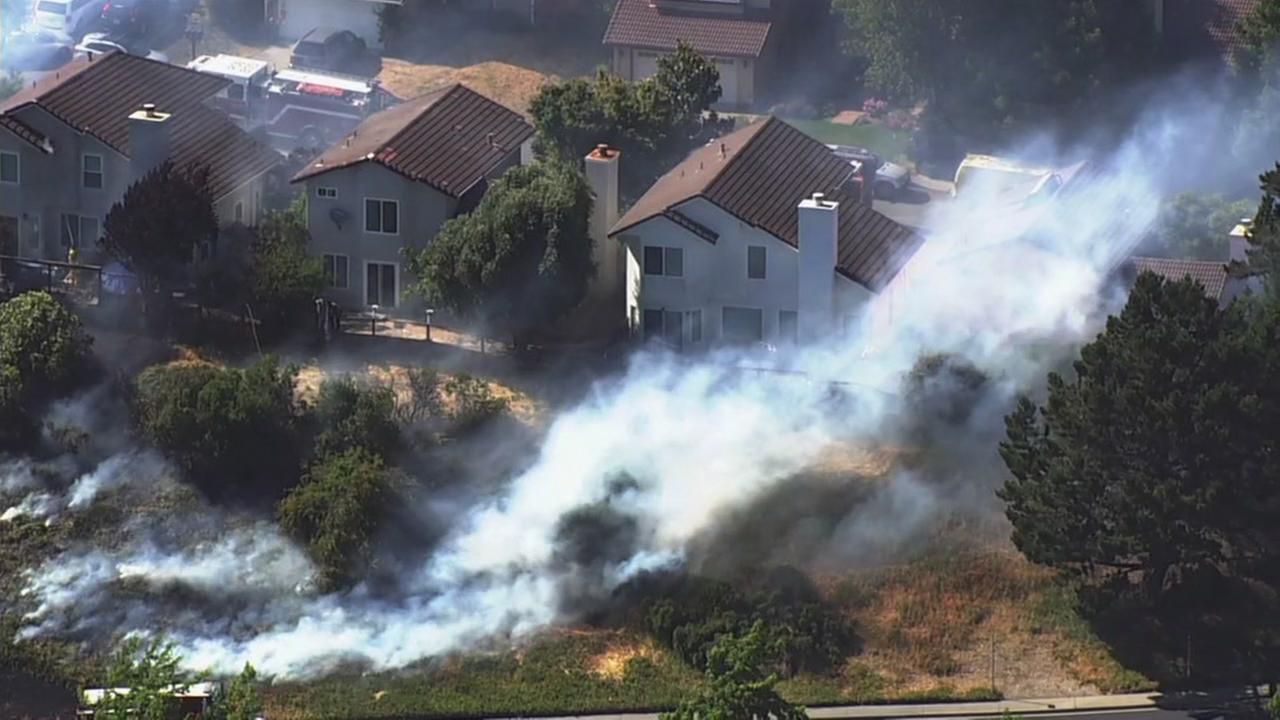 A fire is seen burning near homes in Pinole, Calif. on Tuesday, June 12, 2018.