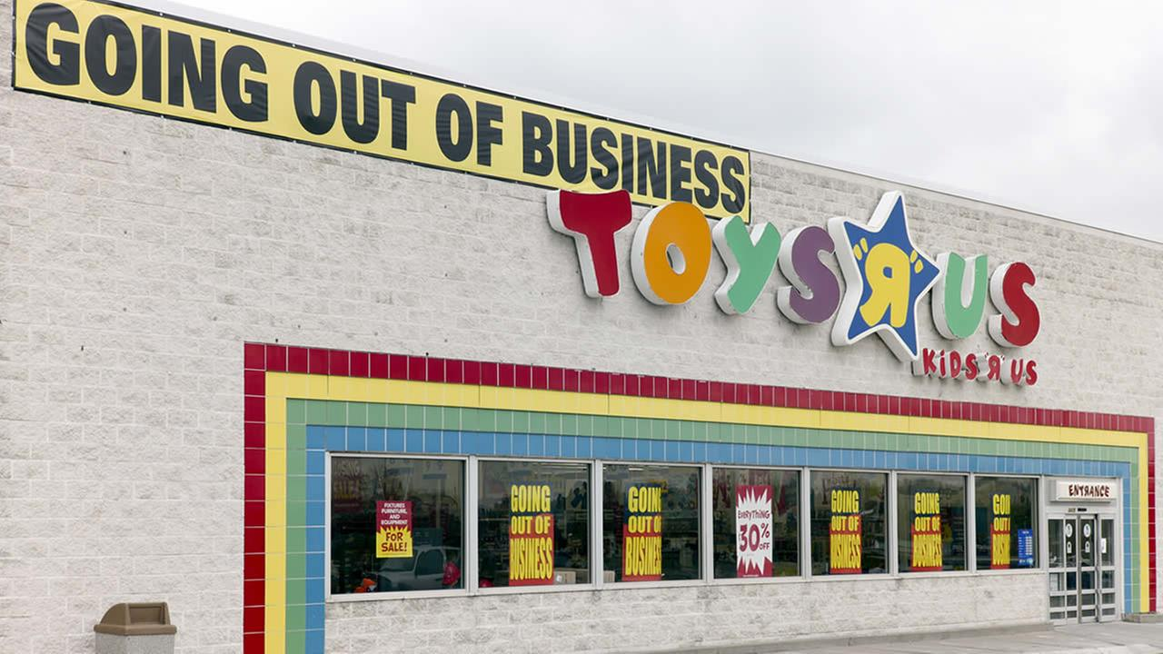 A Going Out Of Business sign hangs over the Toys R Us store logo in Omaha, Neb., Monday, April 9, 2018. (AP Photo/Nati Harnik)