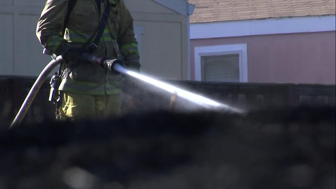 A firefighter works on a suspicious fire in San Jose, Calif. on Wednesday, June 27, 2018.