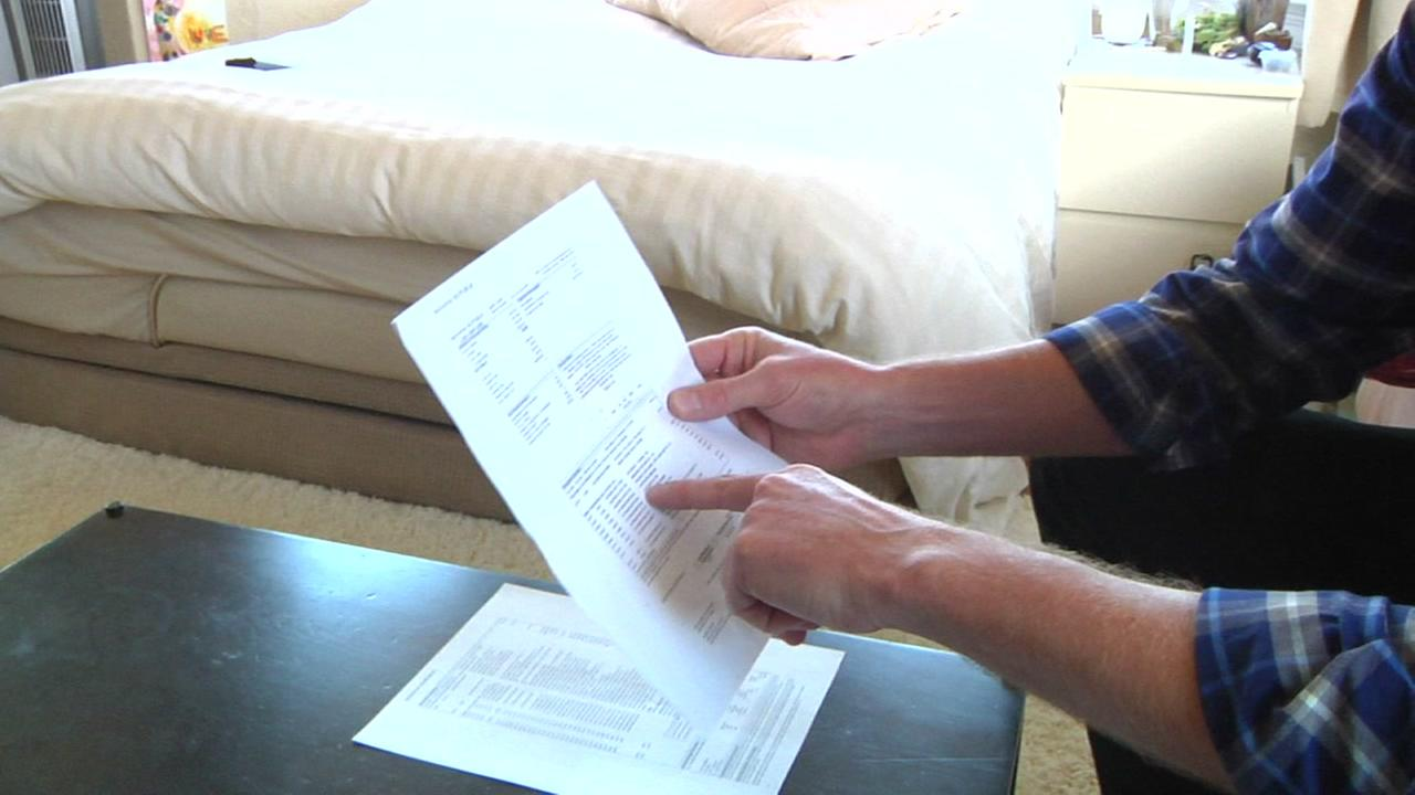 Mark Crane points to his credit card statement while at his San Francisco home.