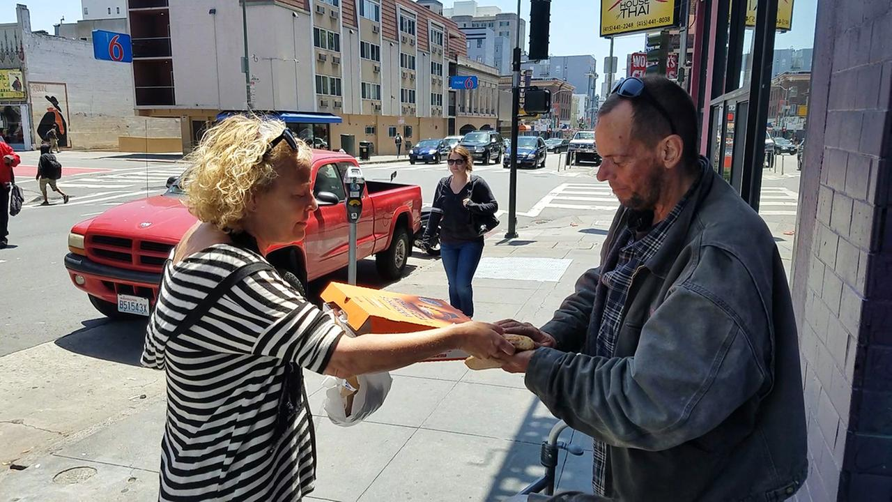 Andrea Carla Michaels hands out a slice of pizza to a homeless man on Polk Street in San Francisco.