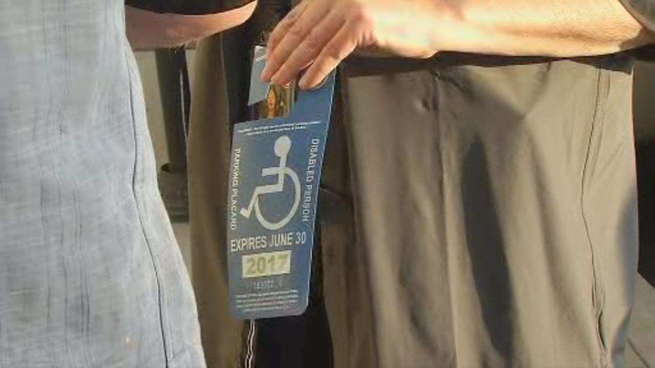 This undated image shows someone holding a DMV issued disabled person (DP) parking placard.