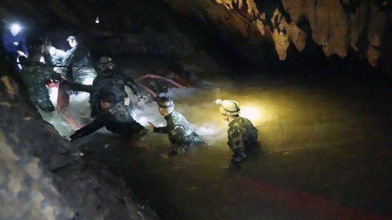 Thai rescue teams walk inside cave complex where 12 boys and their soccer coach went missing, in Mae Sai, Chiang Rai province, in northern Thailand, Monday, July 2, 2018.