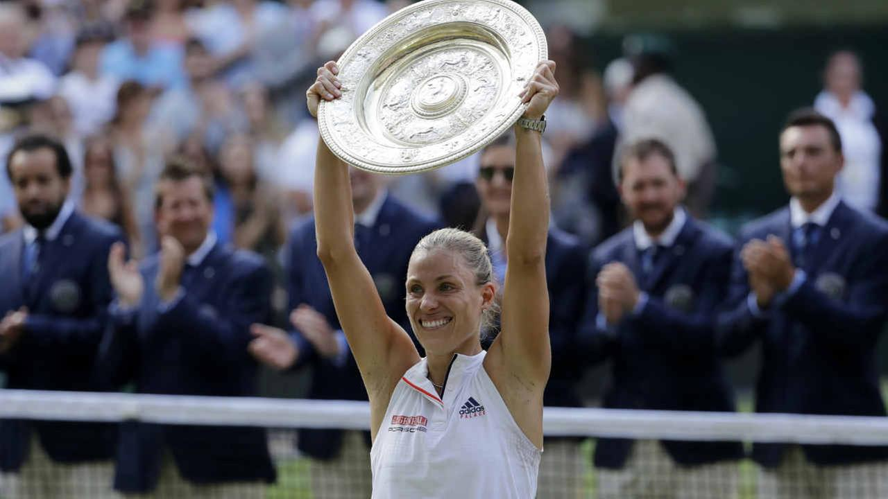 Angelique Kerber holds up the trophy after defeating Serena Williams in their womens singles final match at the Wimbledon Tennis Championships, in London, Saturday July 14, 2018.