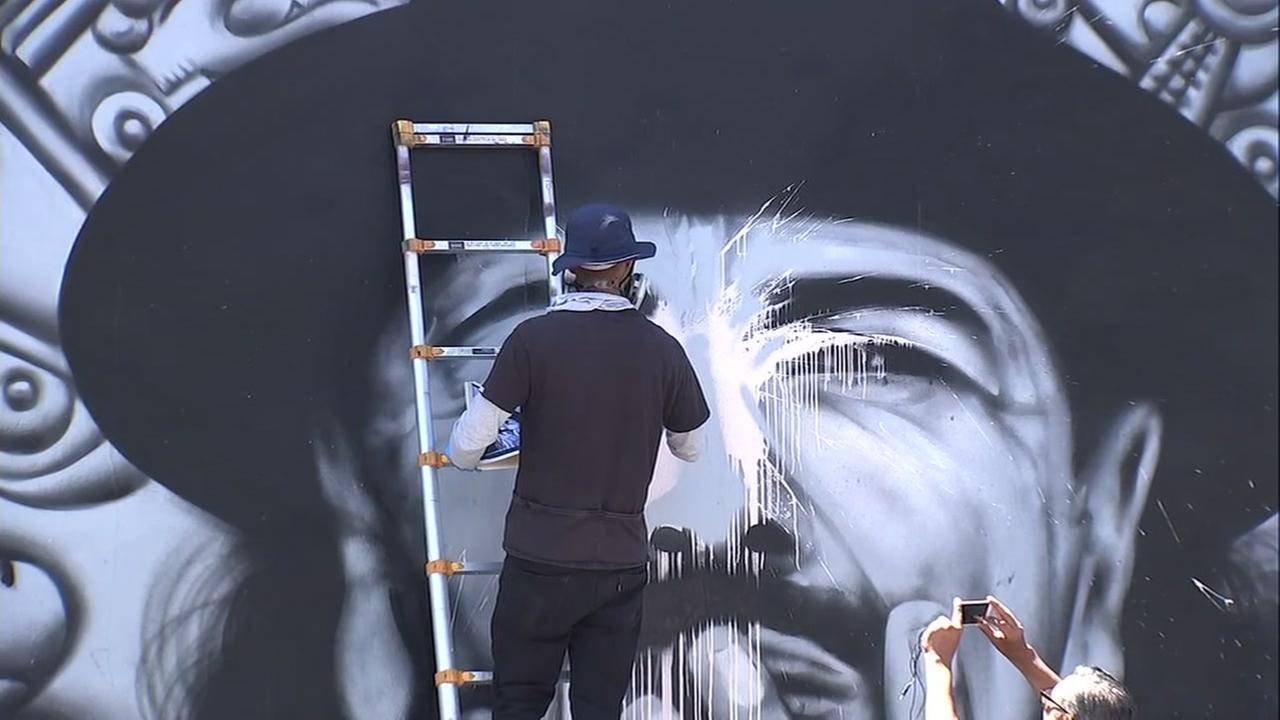 Mel Waters fixes damage to his Carlos Santana mural in San Franciscos Mission District on July 14, 2018.