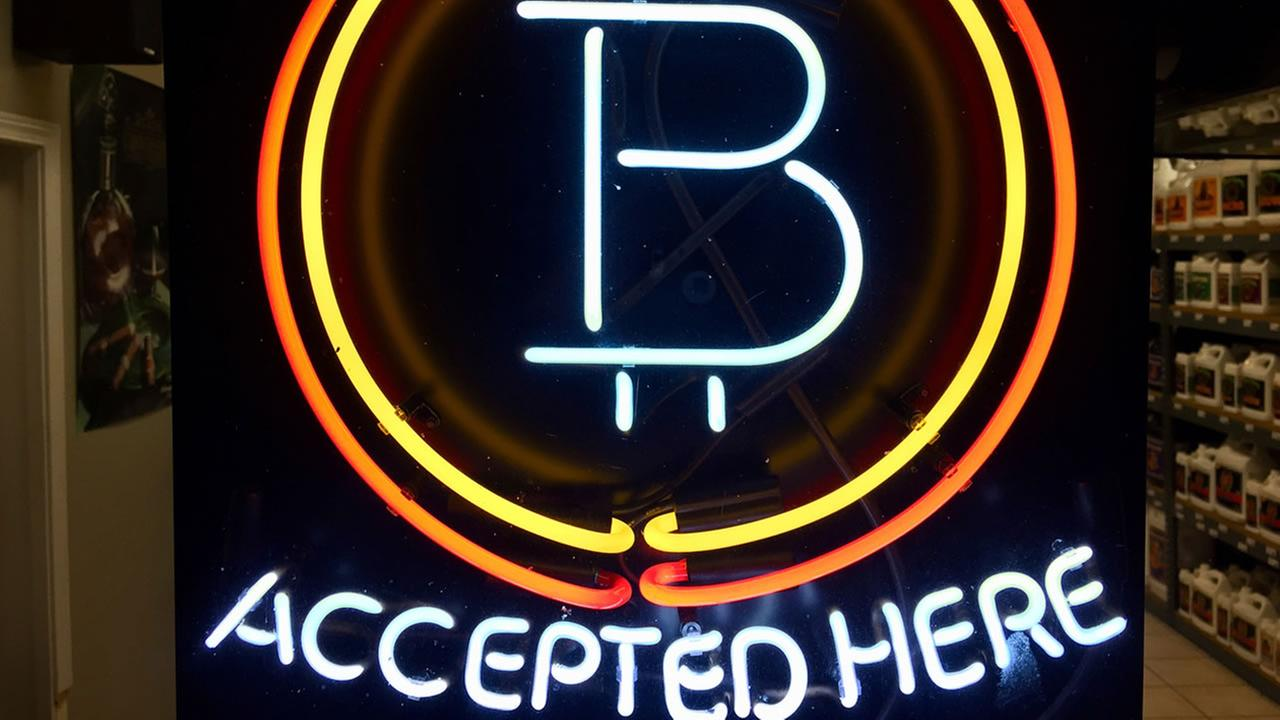 In this Feb. 7, 2018 file photo, a neon sign hanging in the window of Healthy Harvest Indoor Gardening in Hillsboro, Ore., shows that the business accepts bitcoin as payment.