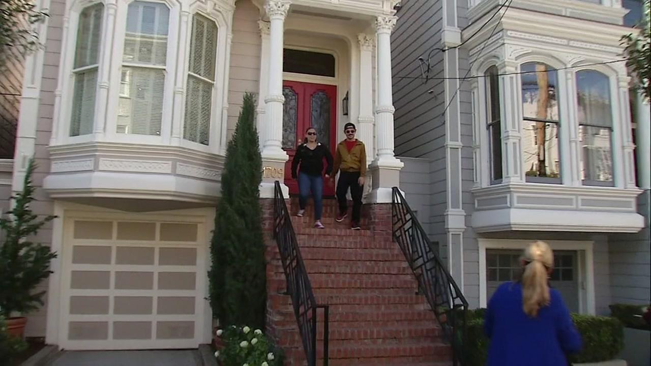 Tourists take a photo in front of the house made famous by the TV show Full House in San Francisco.