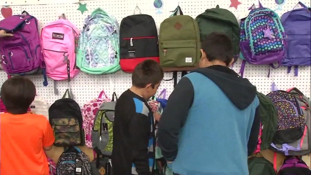 FILE -- Undated photo of kids looking at backpacks at Sacred Heart Community Service in San Jose, California.