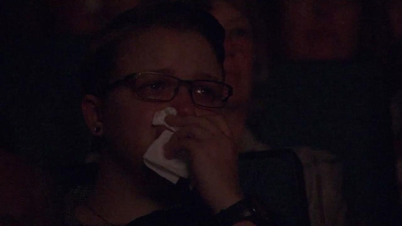 A woman cries while watching Urban Inferno, a documentary about the North Bay Fires on Thursday, July 19, 2018.