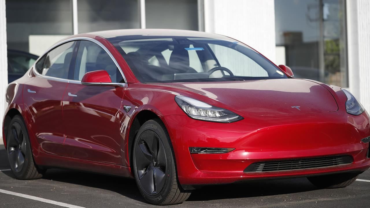 In this Sunday, May 27, 2018, photograph, a 2018 Model 3 sedan sits at a Tesla dealership in Littleton, Colo.